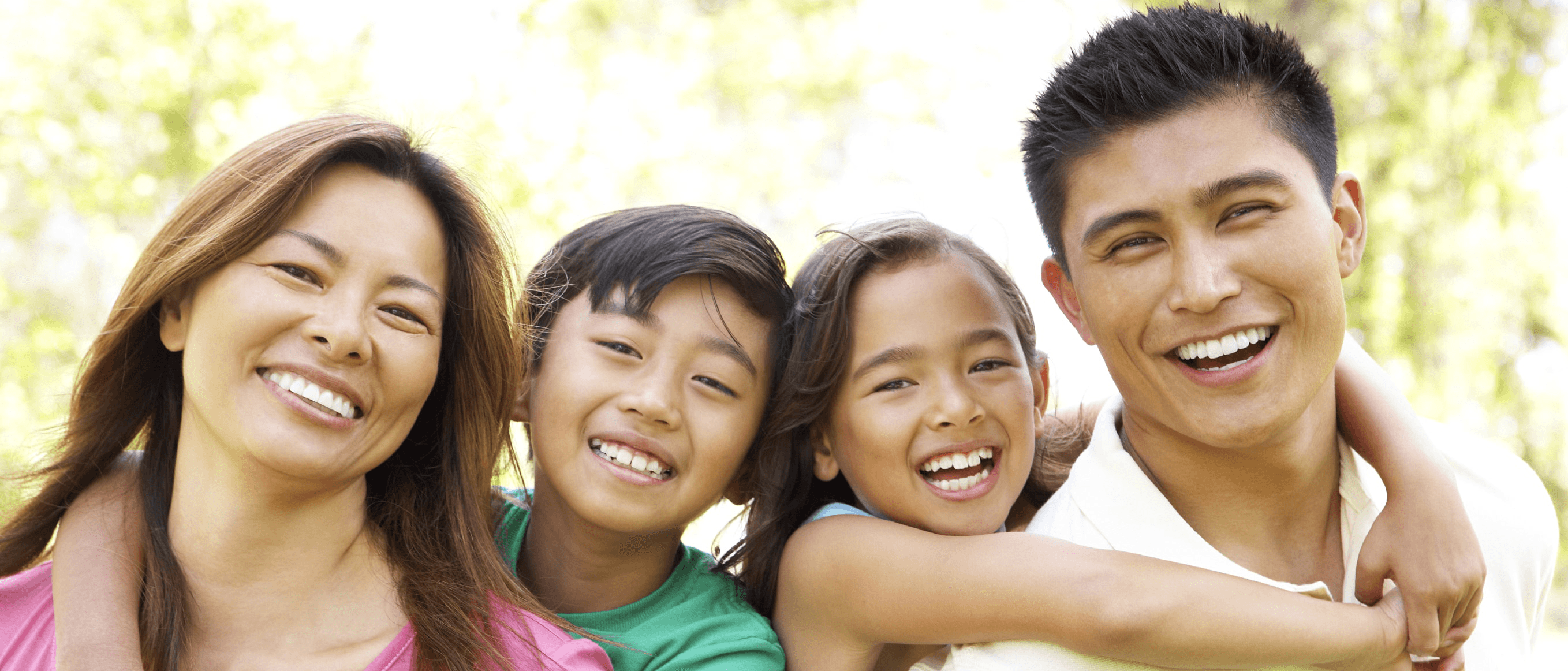 Family smiling with beautiful, white, straight teeth.